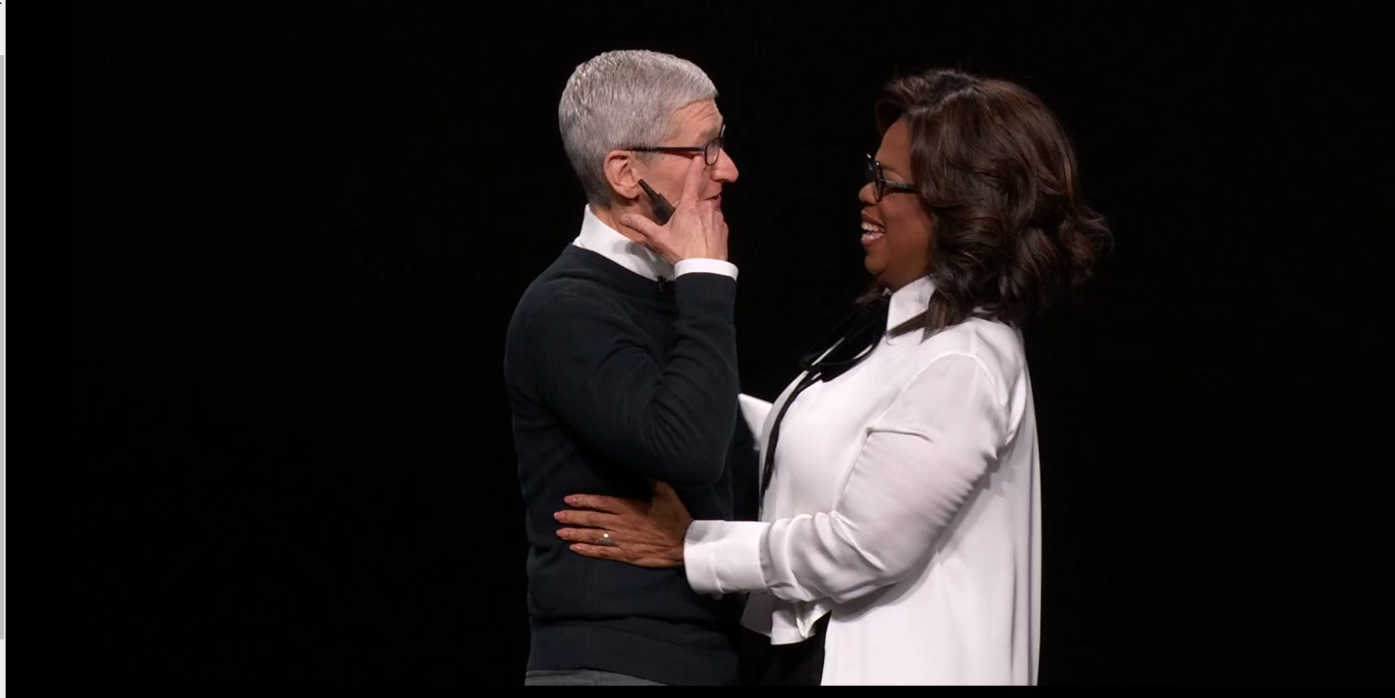 Tim Cook and Oprah embrace on stage.